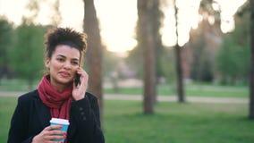 Smartphone de fala da menina atrativa da raça misturada e café bebendo no parque da cidade com sacos Jovem mulher após a compra s filme