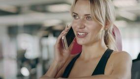 Smartphone de fala da mulher bonita no gym da aptidão Menina de sorriso que tem a ruptura vídeos de arquivo