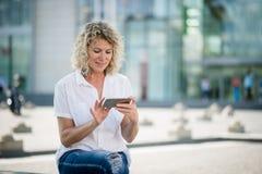 Smartphone de funcionamiento sonriente maduro de la mujer foto de archivo libre de regalías