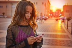 Smartphone de la charla de la muchacha que manda un SMS adolescente en la puesta del sol Imágenes de archivo libres de regalías