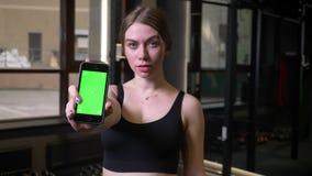 Smartphone de la demostración de Sportsgirl con la pantalla del verde del chromakey en la cámara que es seria y concentrada en gi almacen de video