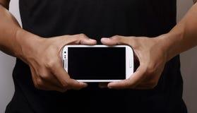 Smartphone de la explotación agrícola de la mano Fotos de archivo
