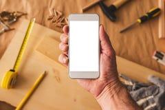 Smartphone de la tenencia del empresario de la artesanía en madera de la pequeña empresa con mofa encima de la pantalla imagenes de archivo