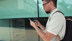 Smartphone de la tenencia del hombre mientras que camina almacen de metraje de vídeo