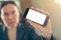 Smartphone de la tenencia de la empresaria con mofa en blanco encima de la pantalla fotos de archivo libres de regalías