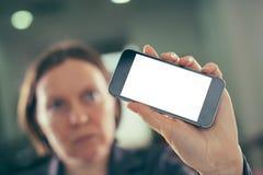 Smartphone de la tenencia de la empresaria con mofa en blanco encima de la pantalla imagen de archivo libre de regalías
