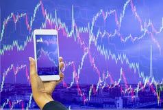 Smartphone de la tenencia de la mano de las mujeres de la exposición doble, pantalla de visualización del gráfico con el fondo de fotografía de archivo libre de regalías