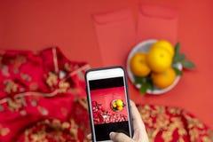 Smartphone de la tenencia de la mano de la mujer a los vestidos del Año Nuevo de las capturas de las naranjas del angpao del bols fotos de archivo