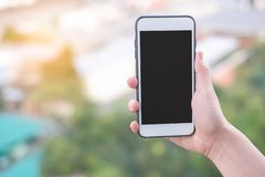 Smartphone de la tenencia de la mano o teléfono móvil con el fondo del edificio de la ciudad y el espacio de la copia imagen de archivo libre de regalías