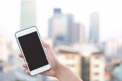 Smartphone de la tenencia de la mano o teléfono móvil con el fondo del edificio de la ciudad y el espacio de la copia fotos de archivo