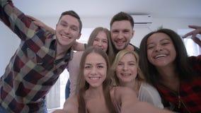 Smartphone de la tenencia de la muchacha que toma la foto del selfie con los amigos alegres y tener partido de la diversión en ca almacen de video