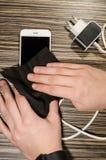 Smartphone de limpieza con un paño de la microfibra imagen de archivo