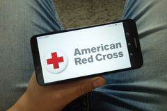 Smartphone de participation d'homme avec le logo américain d'ARC de Croix-Rouge photos libres de droits