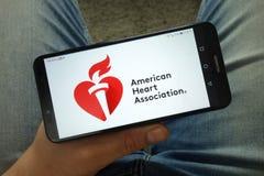 Smartphone de participation d'homme avec le logo américain de l'association AHA de coeur photo libre de droits