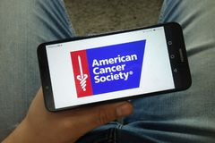 Smartphone de participation d'homme avec le logo américain de l'Association du cancer ACS photographie stock