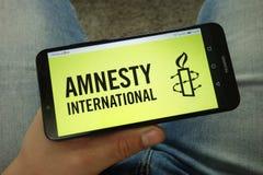 Smartphone de participation d'homme avec le logo d'organisation d'Amnesty International photo libre de droits