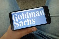 Smartphone de participation d'homme avec le logo de soci?t? de Goldman Sachs photo libre de droits
