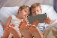 Smartphone de participation de deux garçons, comprimé se reposant sur la chaise, foyer sur les pieds des enfants images libres de droits