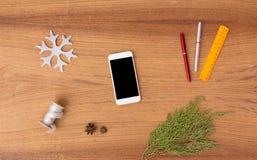 Smartphone-de samenstelling van modelkerstmis spartakken en decoratie op houten achtergrond stock afbeeldingen