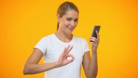 Smartphone de sorriso da terra arrendada do gesto da aprovação da exibição da jovem mulher à disposição, dinheiro para trás filme