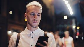 Smartphone de sourire d'usingn d'homme dans la ville de nuit Jeune homme beau à l'aide du smartphone la nuit Communication de mob clips vidéos