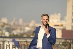 Smartphone de sourire heureux d'utilisation d'homme d'affaires pour l'appel ou le service de mini-messages visuel, fond d'horizon images stock