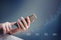 Smartphone de utilização fêmea a verificar e trabalhar com gráfico não especificado fotografia de stock royalty free