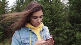 Smartphone de utilização misto do tela táctil do jovem adolescente quando na natureza Moderno que usa meios sociais e sorrindo ao video estoque