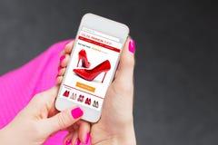 Smartphone de utilização fêmea para comprar em linha sapatas Imagens de Stock