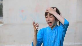 Smartphone de vidro quebrado da tela à disposição da menina da virada, fundo branco filme