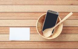 Smartphone de vue supérieure dans la cuvette en bois sur le fond en bois de planche Images stock