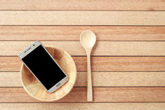 Smartphone de vue supérieure dans la cuvette en bois sur le fond en bois de planche Photographie stock