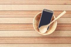 Smartphone de vue supérieure dans la cuvette en bois sur le fond en bois de planche Photo libre de droits