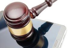 Smartphone debajo del mazo del juez sobre él - el estudio tiró en blanco imagen de archivo libre de regalías