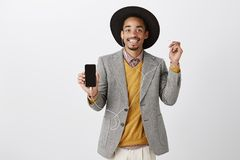 Smartphone definitely worth buying. Portrait of satisfied good-looking african customer in classy suit and hat, showing. Smartphone, taking off earbud while Royalty Free Stock Photography