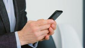 Smartphone del hombre que manda un SMS a los apps digitales que hacen negocio metrajes