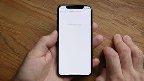 smartphone del iPhone XS del POV del hombre por el Apple Computer que pone al día el IOS metrajes