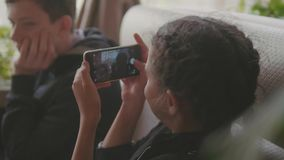 Smartphone del juego de niños en un café de los alimentos de preparación rápida la muchacha toma imágenes del adolescente del muc almacen de metraje de vídeo