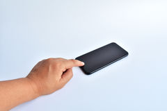 smartphone del nero di tocco della mano su fondo bianco Immagine Stock Libera da Diritti