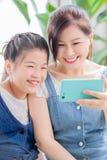 Smartphone del uso de la hija y de la mam? fotos de archivo