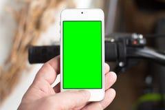 Smartphone del uso de la mano del ` s del hombre mientras que él defiende cerca el camino con las bicis Imagen de archivo libre de regalías