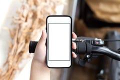 Smartphone del uso de la mano del ` s del muchacho mientras que él defiende cerca el camino con las bicis Fotos de archivo