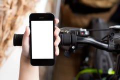 Smartphone del uso de la mano del ` s del muchacho mientras que él defiende cerca el camino con las bicis Imagenes de archivo