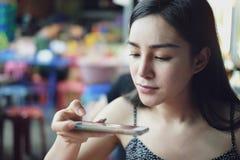 Smartphone del uso de la muchacha y tomar mensajería de la foto fotos de archivo