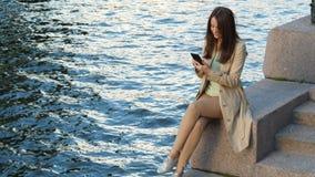 Smartphone del uso de la mujer de negocios que se sienta en el muelle del río almacen de video