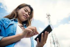 Smartphone del uso de las mujeres y remolque de la telecomunicación por satélite imagenes de archivo