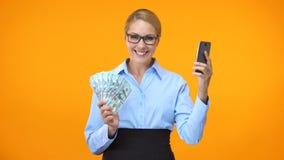 Smartphone della tenuta del vestito della donna attraente e dollari convenzionali sorpresi, attività bancarie archivi video