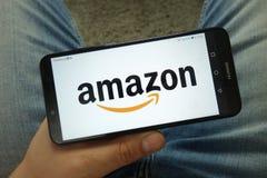 Smartphone della tenuta dell'uomo con Amazon logo della società di COM immagine stock