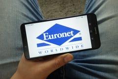 Smartphone della tenuta dell'uomo con l'EURONET universalmente, inc Marchio dell'azienda immagini stock