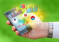 Smartphone della tenuta dell'uomo di affari con i simboli del grafico Immagini Stock